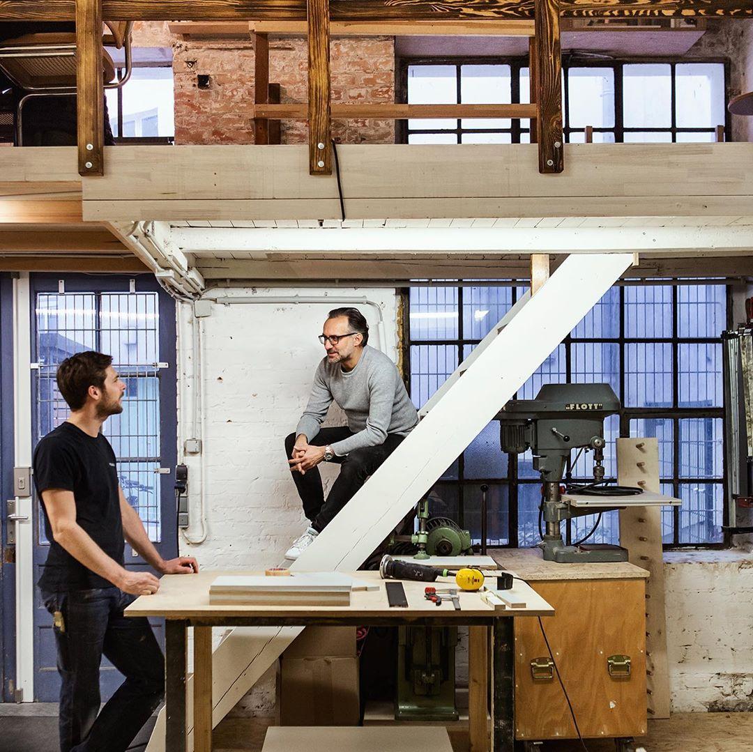 Auschnitt von einer kleinen Werkstatt mit den Designer Olaf Schroeder, der an einer Treppe sitzt, und mit seinen Kollegen, der vor einem Tisch mit ihm spricht