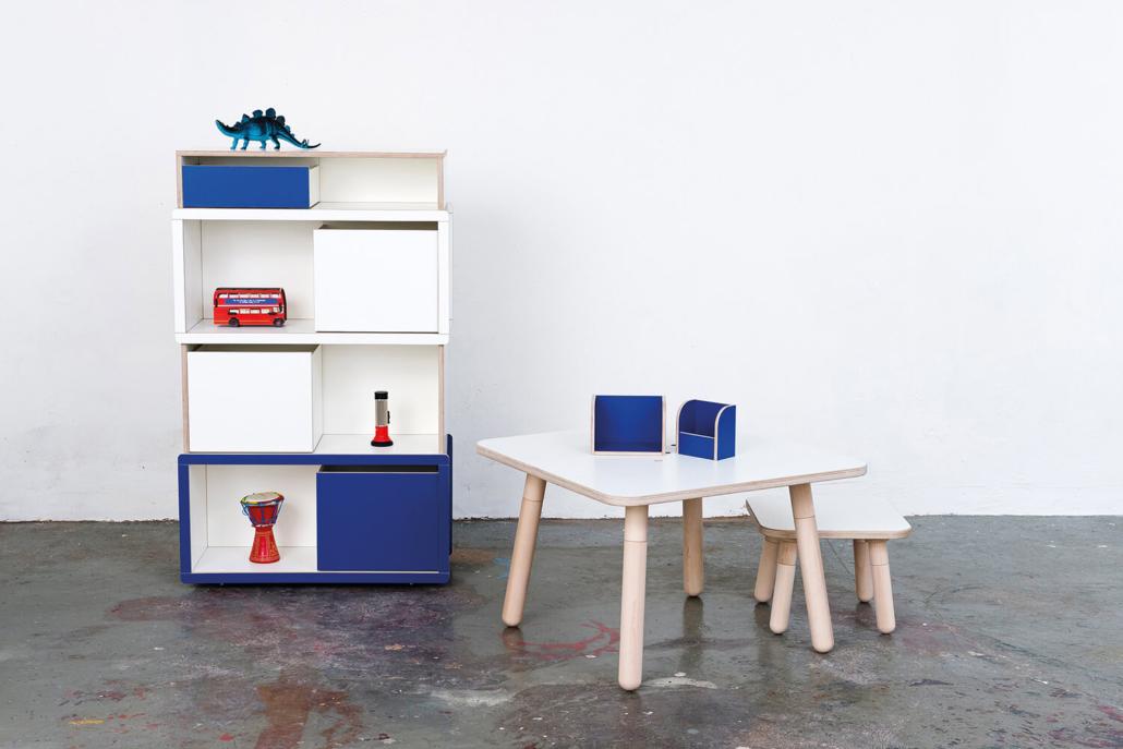 blauer brick for kids Regal mit Spielzeug auf der linken Seite und ein weiß lackierter growing table auf Oberfläche mit der zwei blauen Tools und weiß lackierten Hocker auf der rechten Seite