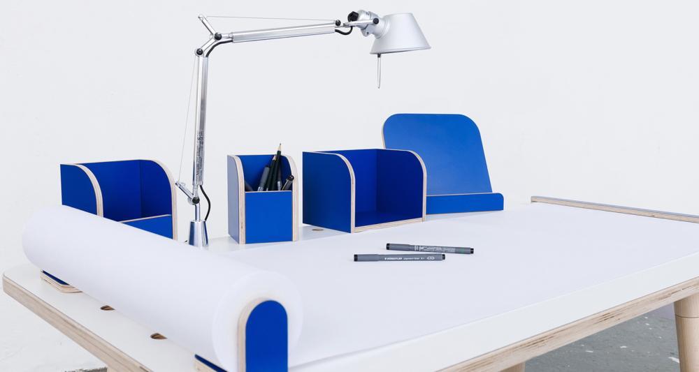 Ansicht auf den rowing table mit weißer Oberfläche und blauen Tools mit einer angebrachten Tischlampe sowie ausgerollten Papierrolle mit Stifen