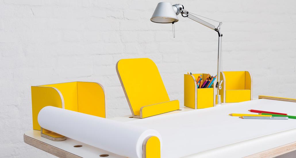 Ansicht auf den growing table mit weißer Oberfläche und gelben Tools mit einer angebrachten Tischlampe sowie ausgerollten Papierrolle mit Stifen