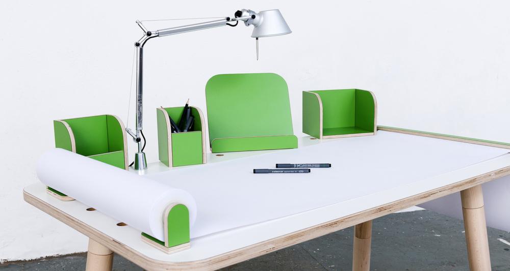 Ansicht auf den growing table mit weißer Oberfläche und grünen Tools mit einer angebrachten Tischlampe sowie ausgerollten Papierrolle mit Stifen