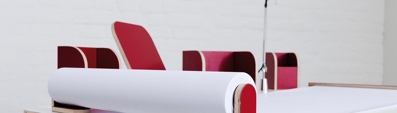 seitliche Ansicht auf den growing table mit weißer Oberfläche und roten Tools mit einer angebrachten Tischlampe sowie ausgerollten Papierrolle