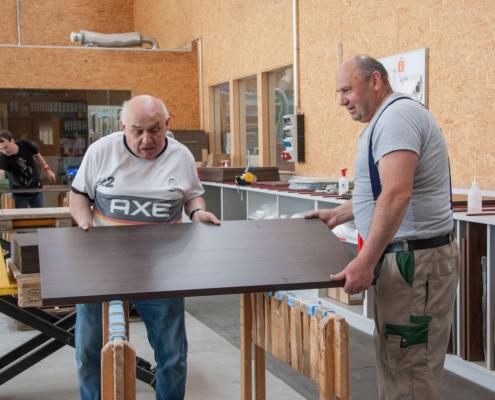 Zwei Mitarbeiter von pure position tragen eine dunkelbraune Holzplatte