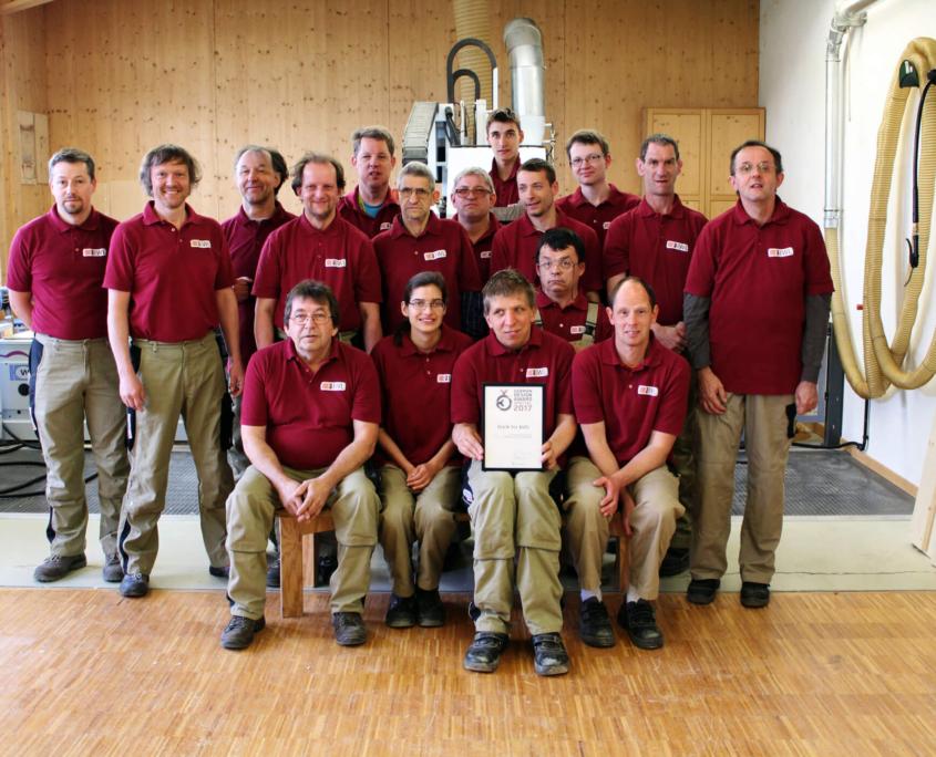 Gruppenfoto Mitarbeiterinnen und Mitarbeiter der IWL halten die Urkunden von der pure position Auszeichnung german design award
