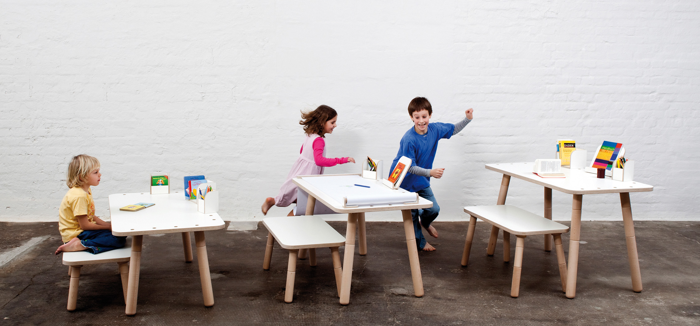 Drei verschiedene Beispiele der Höhenverstellung beim growing table mit spielenden Kindern im Hintergrund