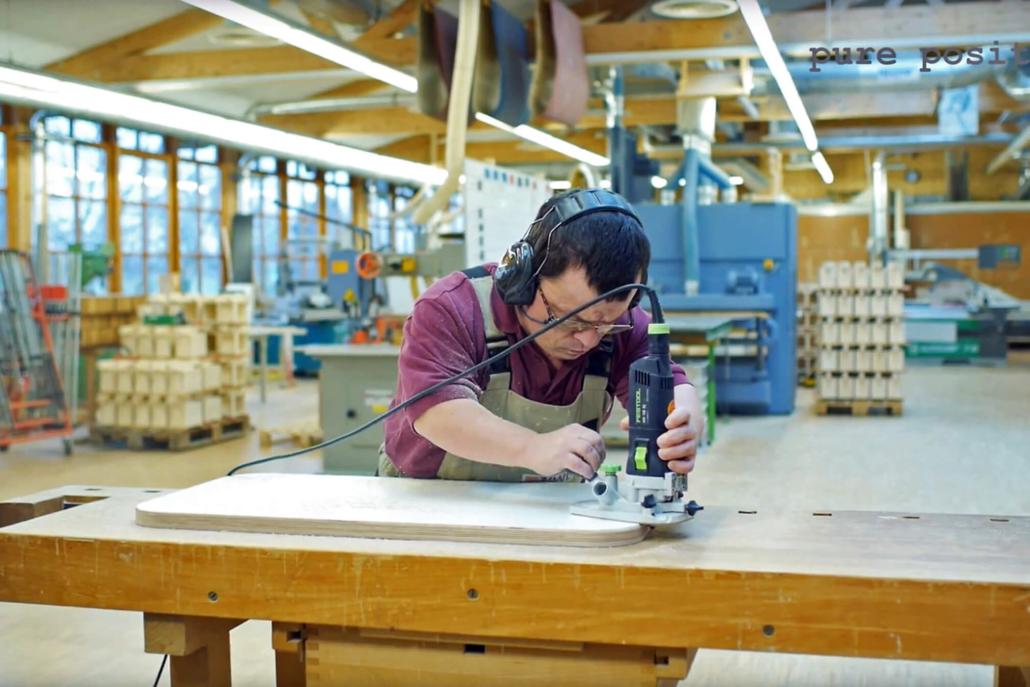 Mitarbeiter von der IWL schleift mit einem Schleifgerät die Oberfläche einer Tischplatte in der Produktion