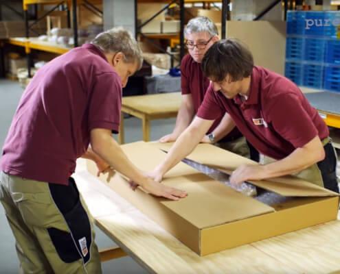 Drei Mitarbeiter von der IWL verpacken Einzelteile eines Möbelstücks ein