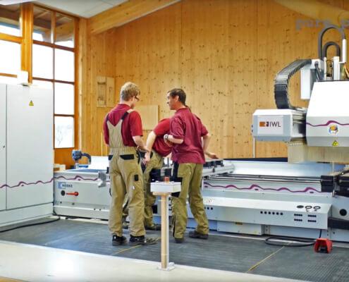 Drei Mitarbeiter von der IWL stehen vor einer Produktionsmaschine in der Produktion