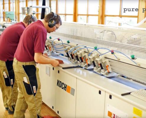 Mitarbeiter von der IWL arbeiten an einer länglichen Bandmaschine ein Holzstück in der Produktion