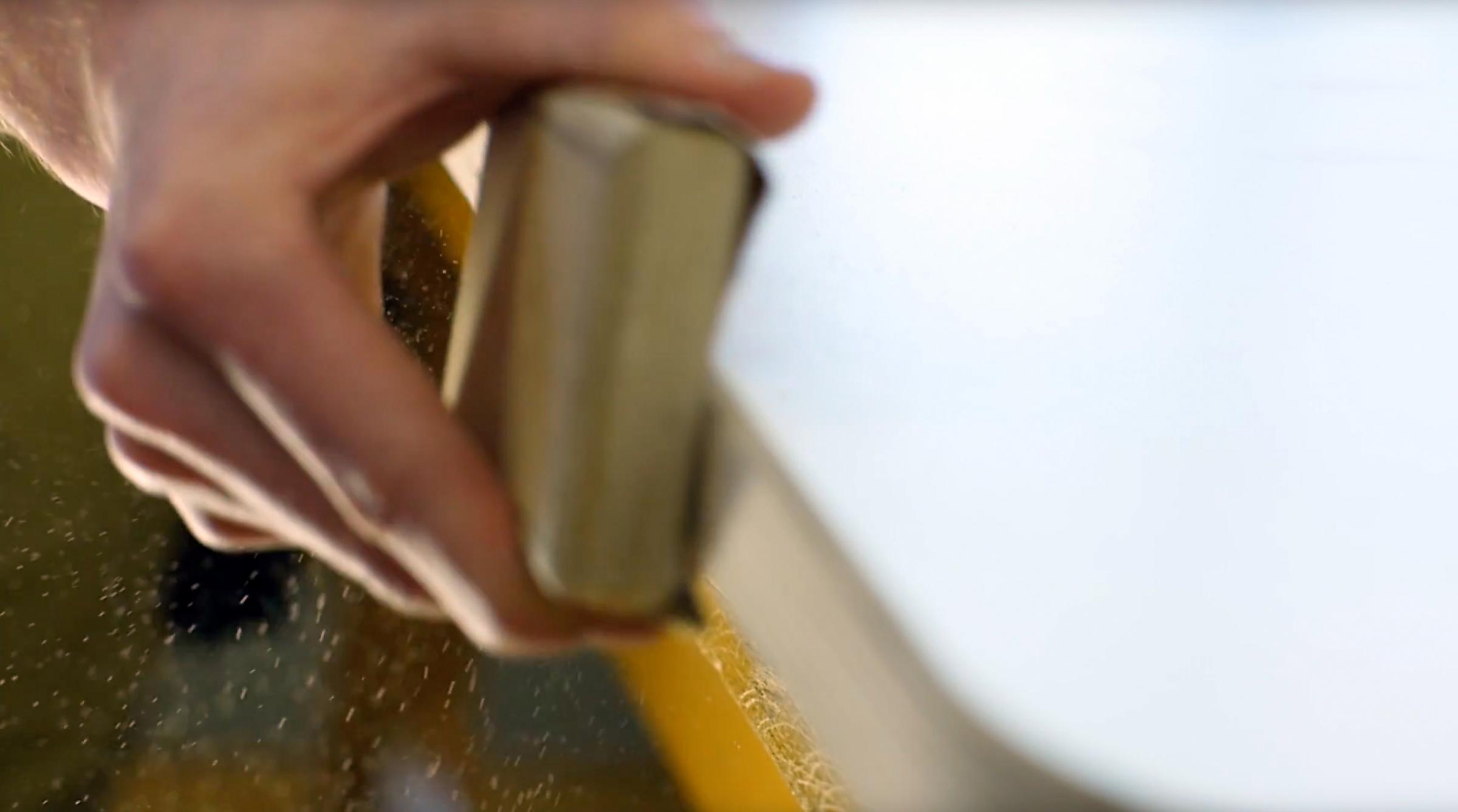 Nahaufname einer Hand von einem Mitarbeiter in der IWL der die Kante einer Tischplatte schleift