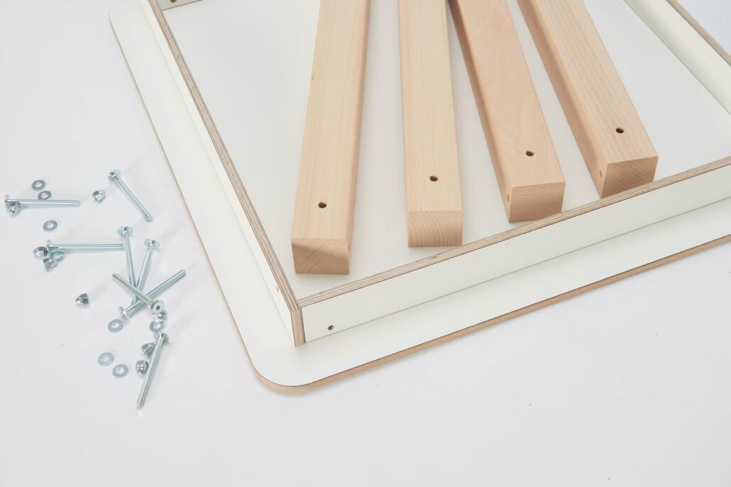 zerlegter Spieltish mit weißer Tischplatte, vier Holzbeinen und Schrauben auf der linken Seite