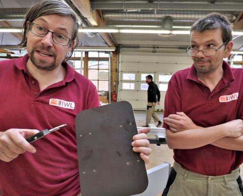 Zwei Mitarbeiter von pure position stehen in der Werkstatt und einer von den spricht in die Kamera mit einem Brett in der Hand