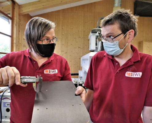 Zwei Mitarbeiter von pure position die die Bohrungsabstände von einem Holzbrett messen