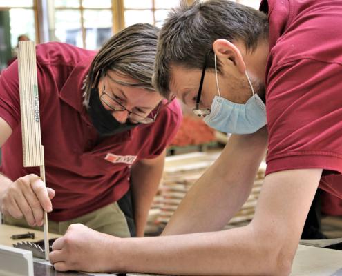 Zwei Mitarbeiter von pure position messen ein Sägeblatt ab