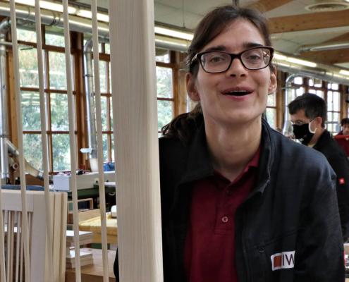 Mitarbeiterin von pure position steht rechts Holzleisten hervor und lacht