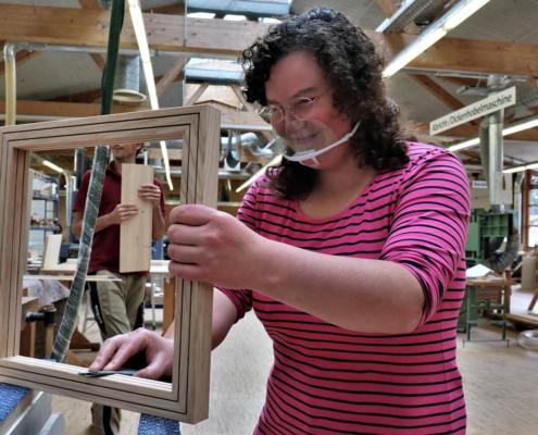 Mitarbeiterin von pure postion schleift einen Holzrahmen