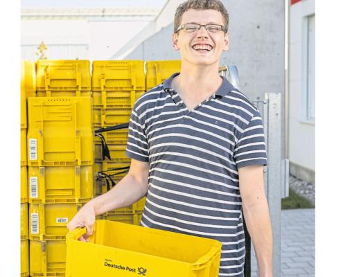 Titelbild vom Magazin FR7 mit einem glücklichen Menschen mit Behinderung der eine gelbe Wanne von der Deutschen Post hält und im Hintergrund mehrere Wannen stehen