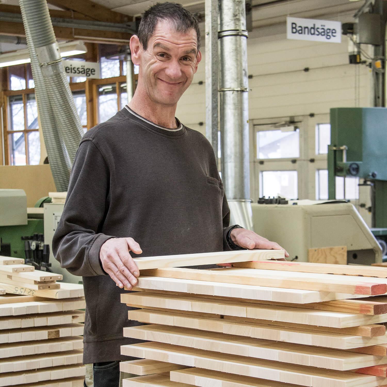 Mitarbeiter von pureposition Lächelt in die Kamera während er einen kleines Holzbrett ablegt