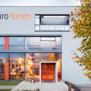 Außenansicht vom Eingang des Gebäudes vom Möbelhändlers büroforum mit großen beleuchteten Fensterfronten, einer weißen Steinwand und mit einer orangenen Eingangstür sowie einer orangenen Säule auf der linken Seite vor den Fensterfronten