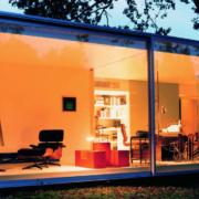 Gebäude mit einer großen beleuchteten Fensterfront wo die Bespielräume mit dem modernen Möbeln von goodform präsentiert werden