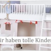 """Werbeanzeige vom Kindermöbelhändler kinderräume mit einem weißen Stockbett für Kinder und vor dem Bett steht ein weißer Schreibtisch. Auf der Werbeanzeige steht rechts ein grauber Werbeslolagen mit der Aufschritt """"Wir haben tolle Kindermöbel"""""""