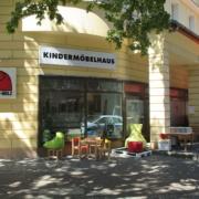 Außenansicht vom Kindermöbelhaus Klein-Holz Laden mit einem Tisch und Stühle für Kinder als Ausstellungsstück am Tag mit Sonnenschein