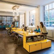 Das moderne Designerbüro und die Entwicklungsstätte von pureposition mit einem langen gelben Tisch, großen Fenstern und einem offenen Raum aus Leipzig