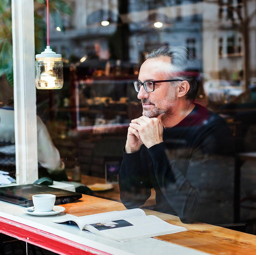 Olaf Schröder, Designer von pureposition, sitzt hinter einer Glaswand in einem Kaffee und schaut dabei raus