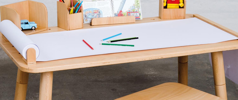 Näherer Einblick auf die Schreibtischoberfläche vom growing table mit der langen Papierrolle sowie mit Stiften und Kinderspielzeug als Deko auf den angesteckten Tools